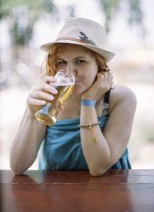 ragazza con cappello che beve birra chiara