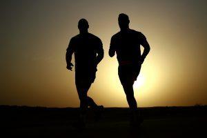 uomini che corrono con il sole dietro